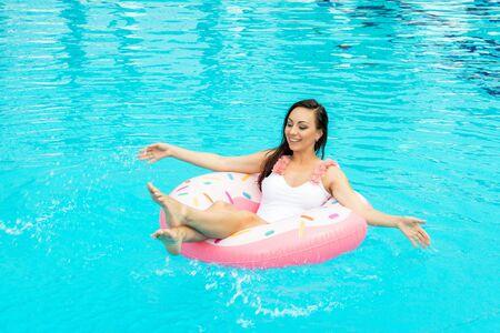 Belle jeune femme en maillot de bain relaxant sur beignet gonflable dans la piscine. Profiter de l'été et s'amuser. Ambiance vacances