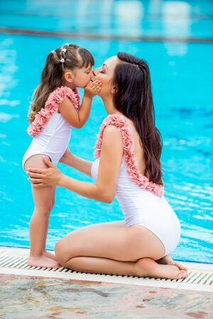 Young Mom with baby daughter in the same white swimsuits sitting on the edge of the pool. Love and kiss. Clothes for summer and sea family look