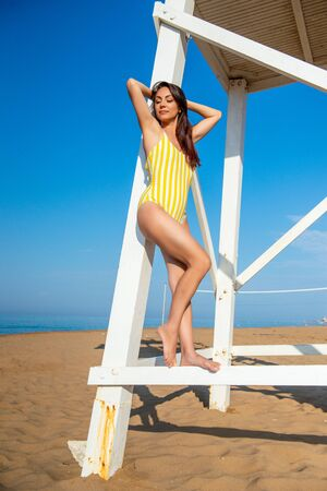 Beautiful slim woman in a yellow swimsuit is standing and posing near the wooden rescue tower on the sea coast. Standard-Bild - 143128410