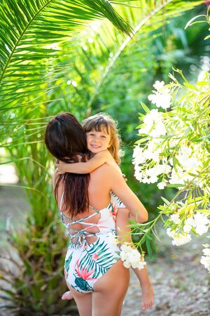 Mom and a small 3 year old daughter with identical swimsuits in the summer in tropical palm trees and flowers. Swimwear and style.