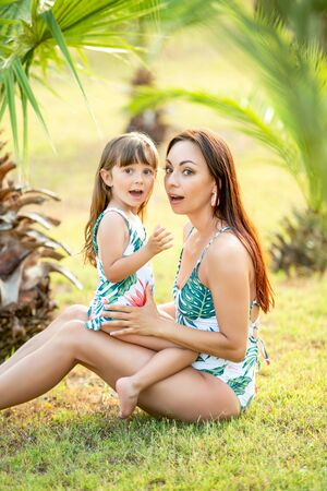 Mom and a small 3 year old daughter with identical swimsuits in the summer in tropical palm trees and flowers. Swimwear and style. Standard-Bild - 143128420