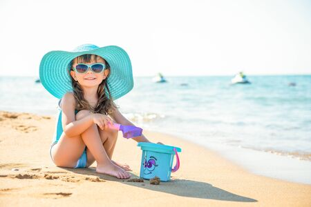 Little child girl fashionista in a blue wide-brimmed hat and sunglasses sits on the sand with a bucket on the seashore. Imagens