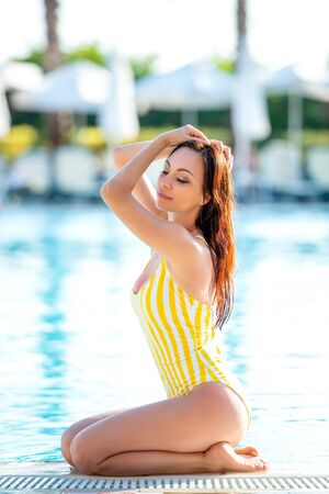 Beautiful young woman in the bathing suit sits on the edge of the pool in a relaxed pose and sunbathes. Enjoying summer, relax. Vacation mood. Standard-Bild - 143128338