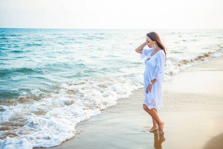 Young woman standing by sea and looking to horizon. Summer holidays vacation travel. Stock Photo