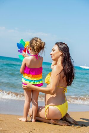 Beautiful young mother in a swimsuit and a small 3 year old daughter with a multi-colored pinwheel rainbow on the sandy beach at sea. Standard-Bild - 143127884