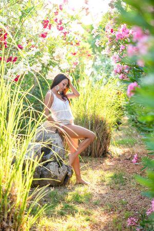 Beautiful brunette girl posing near a stone in a tropical garden with flowers. Standard-Bild - 143127902
