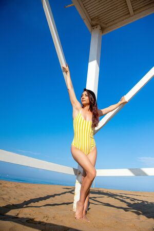 Beautiful slim woman in a yellow swimsuit is standing and posing near the wooden rescue tower on the sea coast. Standard-Bild - 143127913