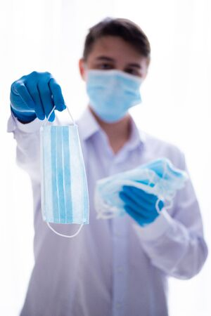 Young man in medical gown and face mask, offering a face mask. Concept infection protection of Covid-19 coronavirus. Stockfoto