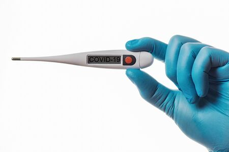 A hand in a rubber glove holds a thermometer. Fever as a sign of Coronovirus Covid-19. Stock fotó