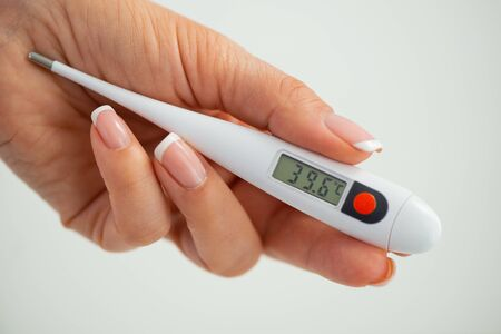 A hand holds a thermometer. Fever as a sign of Coronovirus Covid-19.