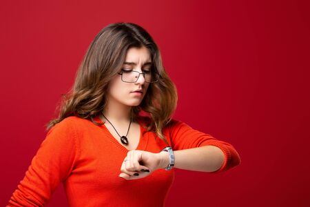 The girl in glasses looks at the watch. Hurry up. Appreciate your time. Do not be late. Isolated on red background