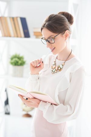 Modern business woman in the office with glasses and with notebook. The girl is wearing elegant suit, a skirt and blouse. Lady boss, female business. Stock Photo - 148098633