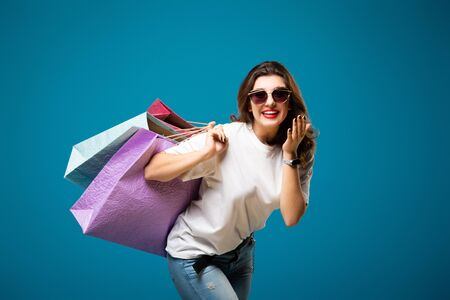 Young stylish beautiful girl in sunglasses is walking with multi-colored shopping bags. Concept shopping and store