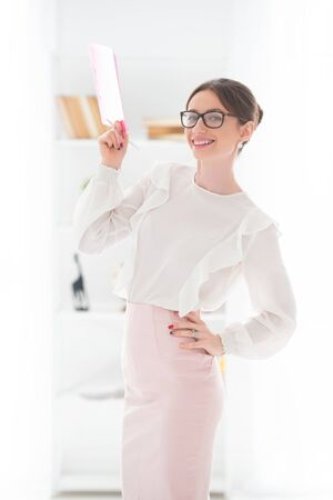 Lady boss, female business. Elegant woman in the office with glasses with a pink folder in hand. Stock Photo