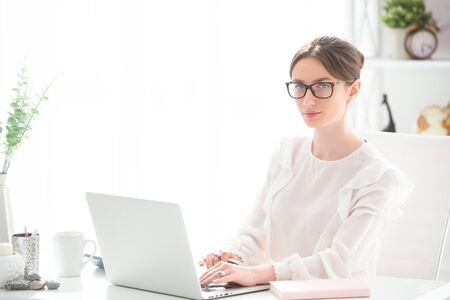 Young woman working at a desk with a laptop in an office. Female business, distant work.