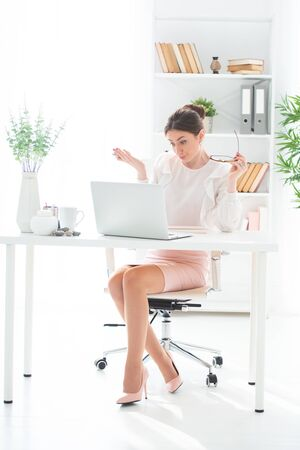 An upset young woman is sitting in an office at a laptop, and is holding her head in her hands. Problems at work.