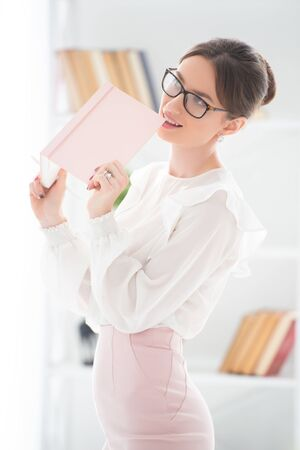 Modern business woman in the office with glasses and with notebook. The girl is wearing elegant suit, a skirt and blouse. Lady boss, female business.