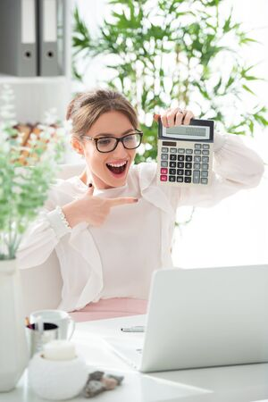 Smiling happy young woman in glasses with calculator in office. Successful balance. Enthusiasm for work. Female online business. Stock Photo