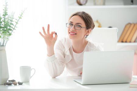 Uśmiechnięta młoda kobieta w biurze jest bardzo zadowolona z udanego zamówienia i pokazuje znak OK. Dobra robota, zwycięstwo. Emocje radości przytłaczają. Zdjęcie Seryjne