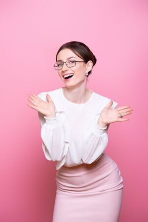 Smiling young businesswoman in glasses motivates success with positive gestures. Isolated on pink background.