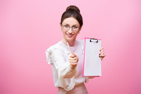 A smiling young woman in glasses holds a clipboard folder in her hands and points to the frame with a pen. Isolated on pink background.