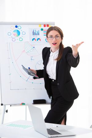 Emotional woman trainer in the office in a business suit shows charts on a flipchart, explains the strategy and motivates for success.