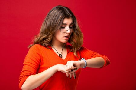 The girl in glasses looks at the watch. Hurry up. Appreciate your time. Do not be late. Isolated on red background. Foto de archivo