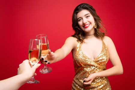 Sexy woman in gold dress with with red lipstick and with champagne in hand over holiday red background. Concept of a New Year holiday, Birthday party. Stock Photo