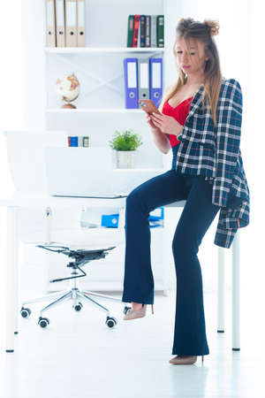 Pretty young woman in a business office with mobile phone in her hands Stock Photo