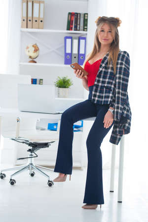 Pretty young woman in a business office with mobile phone in her hands.