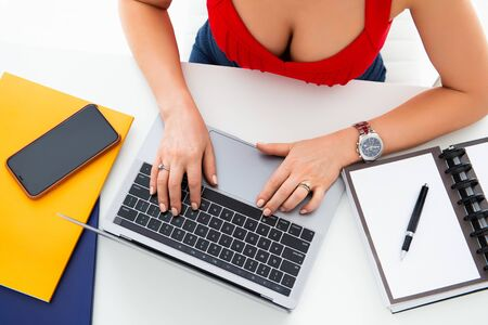 Closeup of a workplace on a desk in an office. Female hands, laptop and mobile phone on the table
