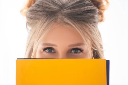Close-up portrait of the face of a blonde girl with a yellow folder. Office, knowledge, student concept Stock Photo