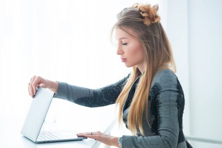 Business woman in a strict business suit works in an office at a desk on a laptop