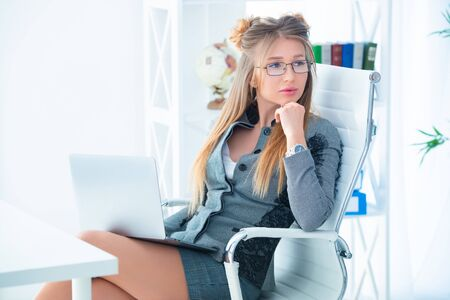 Business woman in glasses and in a strict business suit works in an office at a desk on a laptop