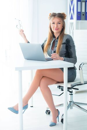 Business woman in a strict business suit works in an office at a desk on a laptop Stock Photo - 149754754