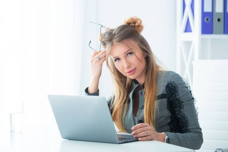 Business woman in a strict business suit works in an office at a desk on a laptop Stock Photo - 149754793
