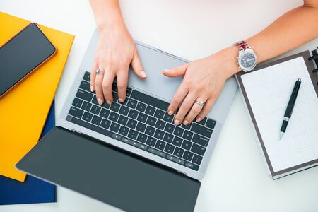 Closeup of a workplace on a desk in an office. Female hands, laptop and mobile phone on the table.