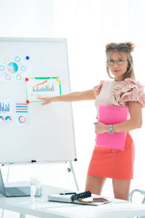 Women's business, conference and revenue planning. Girl businesswoman in office near flipchart shows graphs of sales growth and corporate profits. Stock Photo - 152792059