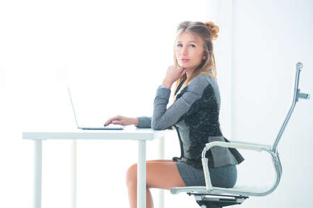 Business woman in a strict business suit works in an office at a desk on a laptop.