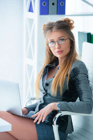 Business woman in glasses and in a strict business suit works in an office at a desk on a laptop. Stock Photo - 152792083