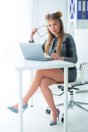 Business woman in a strict business suit works in an office at a desk on a laptop. Stock Photo - 152792084