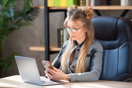 Stylish business woman in glasses and in a fashionable business suit in the interior of the office. Lady Boss, Head, Female Business. Stock Photo