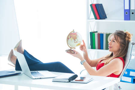 Young business woman sits in the office with legs on the table and holds a globe in her hands. I want a vacation and travel. Foto de archivo