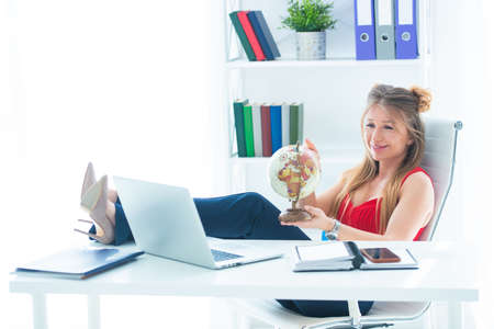 Young business woman sits in the office with legs on the table and holds a globe in her hands. I want a vacation and travel. Stock Photo