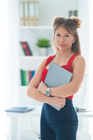 The girl in the office holds a laptop in her hands. Remote work online, female business.