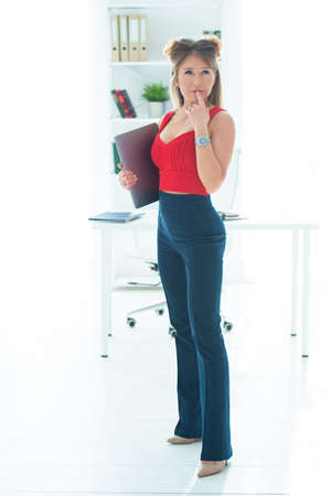 The girl in the office holds folders in her hands. Remote work online, female business. Stock Photo