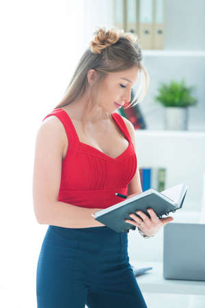 Beautiful young woman in a red top and pants in the office holds a business notebook in her hands. Stock Photo
