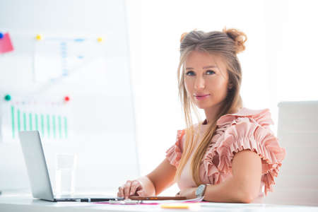 Beautiful young woman in an office is talking via a conference call laptop. Mobile work at home, modern devices. Stock Photo - 152792126