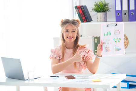 Successful business woman working in an office at a table, showing a graph of profit and sales growth. Stock Photo