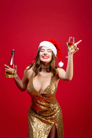 Girl in a gold dress and a Christmas hat drinks champagne on a red background. Concept of a New Year holiday party